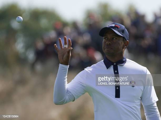 TOPSHOT US golfer Tiger Woods catches a ball during his fourball match on the second day of the 42nd Ryder Cup at Le Golf National Course at...