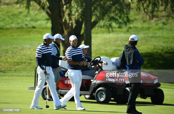 US golfer Tiger Woods chats to teammate US golfer Patrick Reed during a practice session ahead of the 42nd Ryder Cup at Le Golf National Course at...