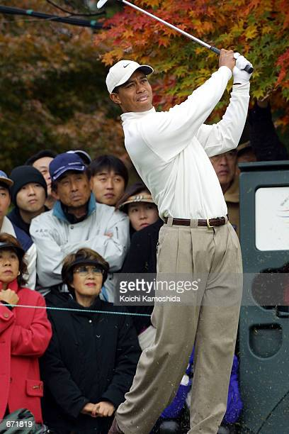 Golfer Tiger Woods follows through on a shot November 17 2001 during the World Golf ChampionshipsEMS World Cup at the Gotemba Golf Course near Tokyo...