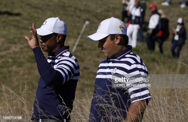 US golfer Tiger Woods gestures as he speaks with US golfer Patrick Reed during a practice session ahead of the 42nd Ryder Cup at Le Golf National...