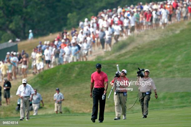 Golfer Tiger Woods is followed by cameramen and fans as he walks up the fairway during the 4th round of the US Open at Oakmont Country Club in...