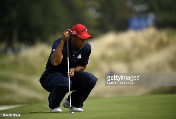 US golfer Tiger Woods lines up a putt on the third day of the 42nd Ryder Cup at Le Golf National Course at SaintQuentinenYvelines southwest of Paris...
