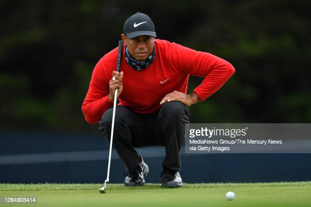 Golfer Tiger Woods lines up his putt on the 13th green during the final round of the 102nd PGA Championship at TPC Harding Park in San Francisco,...
