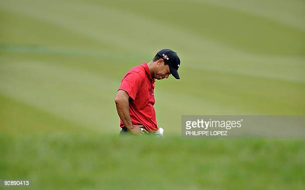 US golfer Tiger Woods looks down after landing in a bunker during the HSBC Champions golf tournament in Shanghai on November 8 2009 US golfer Phil...