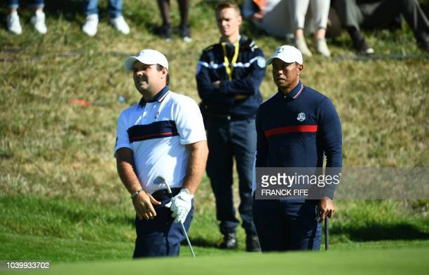 Golfer Tiger Woods looks on as teammate US golfer Patrick Reed plays a shot out of a bunker during a practice session ahead of the 42nd Ryder Cup at...