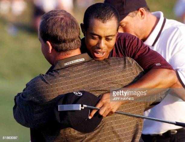 Golfer Tiger Woods of the US hugs Bob May on the 18th hole after their playoff 20 August 2000 in the 82nd PGA Championship at Valhalla Golf Club in...