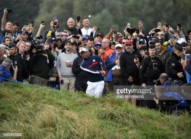 US golfer Tiger Woods plays a chip shot during his fourball match on the first day of the 42nd Ryder Cup at Le Golf National Course at...