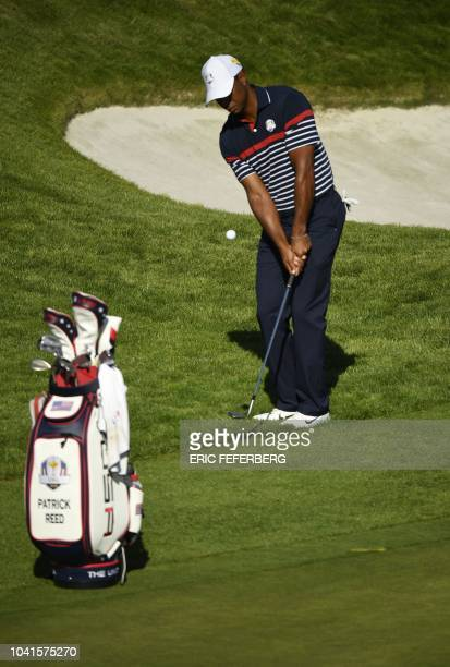 US golfer Tiger Woods plays a chip shot next to teammate Patrick Reed's golf bag during a practice session ahead of the 42nd Ryder Cup at Le Golf...