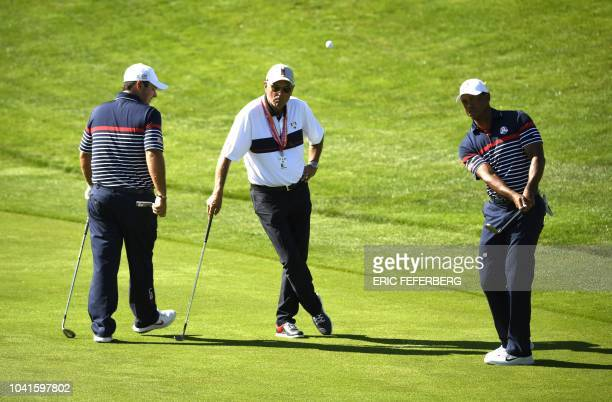 US golfer Tiger Woods plays a fairway shot as US golfer Patrick Reed looks on during a practice session ahead of the 42nd Ryder Cup at Le Golf...