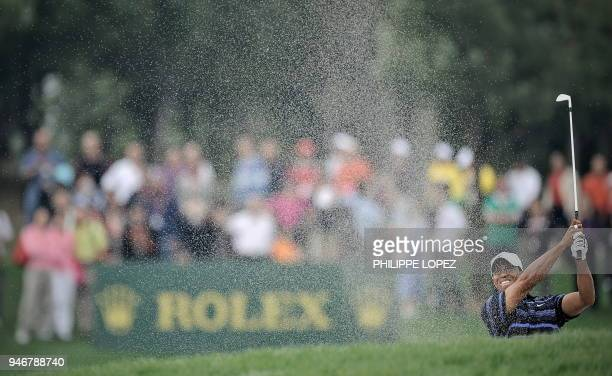 US golfer Tiger Woods plays a shot from a bunker during the HSBC Champions golf tournament in Shanghai on November 7 2009 US golfer Phil Mickelson...