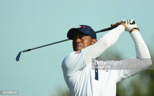 US golfer Tiger Woods plays a tee shot during his foursomes match on the second day of the 42nd Ryder Cup at Le Golf National Course at...