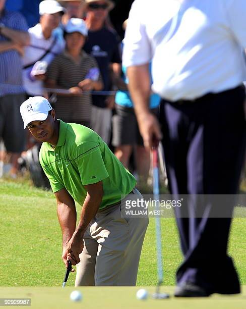US golfer Tiger Woods putts a ball towards Australian golfer Craig Parry during his first practice round for the Australian Masters his first...