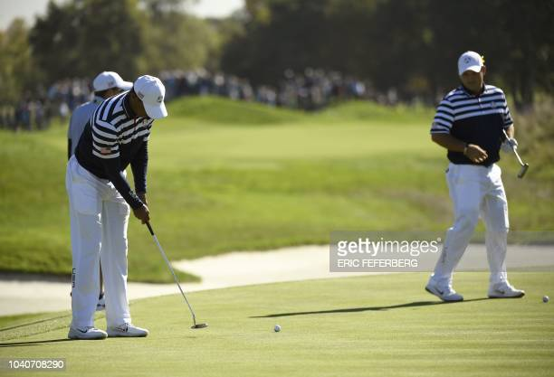 US golfer Tiger Woods putts as US golfer Patrick Reed looks on during a practice session ahead of the 42nd Ryder Cup at Le Golf National Course at...