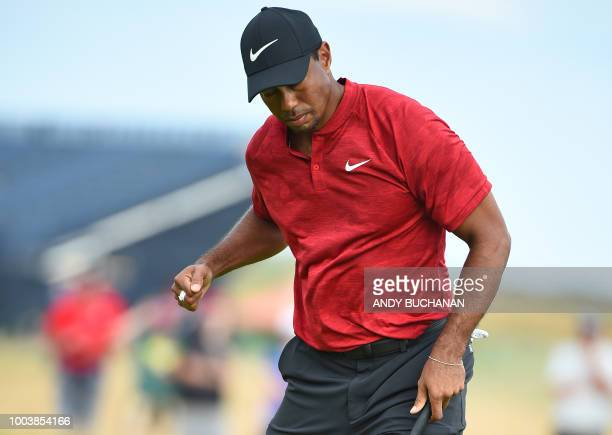 US golfer Tiger Woods reacts after holing his birdie putt on the 14th green during his final round on day 4 of The 147th Open golf Championship at...