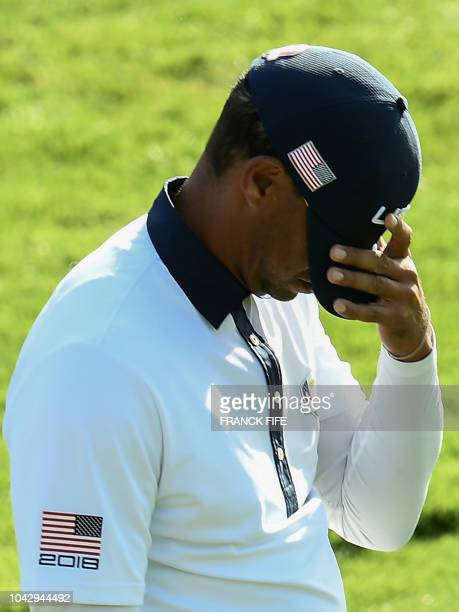 TOPSHOT US golfer Tiger Woods reacts after losing during his foursomes match on the second day of the 42nd Ryder Cup at Le Golf National Course at...