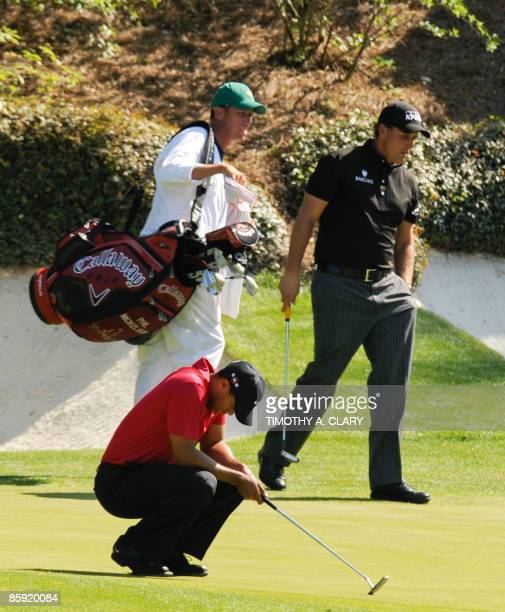 Golfer Tiger Woods reacts after missing a putt for eagle on the thirteenth green as compatriot Phil Mickelson prepares to putt during the final round...