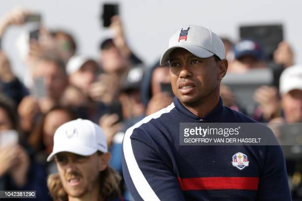 US golfer Tiger Woods reacts next to Europe's English golfer Tommy Fleetwood during his fourball match on the first day of the 42nd Ryder Cup at Le...