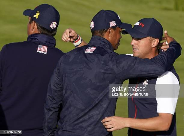 US golfer Tiger Woods reacts with US golfer Justin Thomas at the end of the second day of the 42nd Ryder Cup at Le Golf National Course at...
