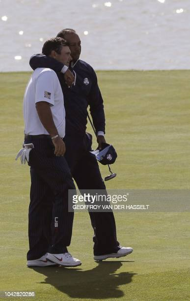 US golfer Tiger Woods reacts with US golfer Patrick Reed during their fourball match on the second day of the 42nd Ryder Cup at Le Golf National...