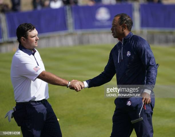 US golfer Tiger Woods shakes hands with US golfer Patrick Reed after their fourball match on the second day of the 42nd Ryder Cup at Le Golf National...