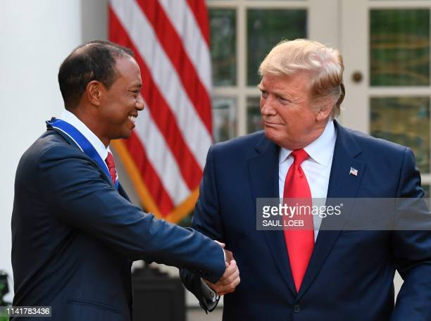 US golfer Tiger Woods shakes hands with US President Donald Trump after he presented him with the Presidential Medal of Freedom during a ceremony in...
