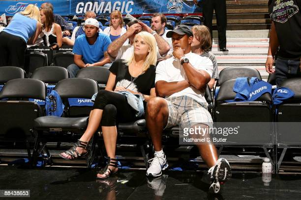 Golfer Tiger Woods sits courtside with his wife Elin as they get set to watch the Los Angeles Lakers play against the Orlando Magic in Game Four of...