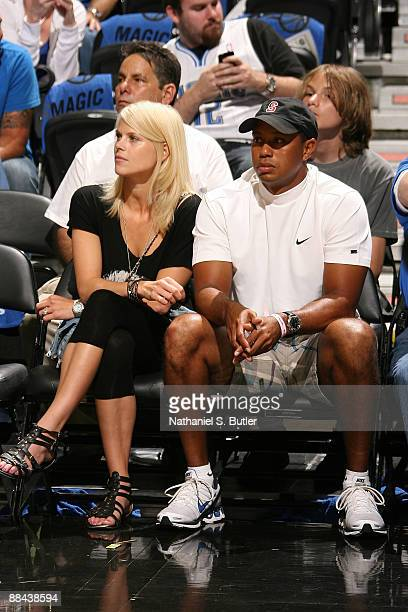 Golfer Tiger Woods sits courtside with his wife Elin as they watch the Los Angeles Lakers play against the Orlando Magic in Game Four of the 2009 NBA...