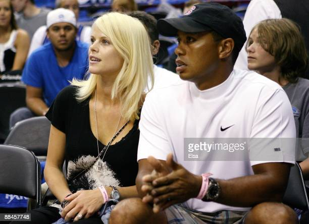 Golfer Tiger Woods sits courtside with his wife Elin during Game Four of the 2009 NBA Finals between the Los Angeles Lakers and the Orlando Magic at...