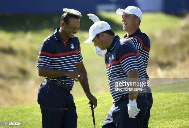 US golfer Tiger Woods smiles with a tuft of grass on his head placed there by US golfer Justin Thomas during a practice session ahead of the 42nd...