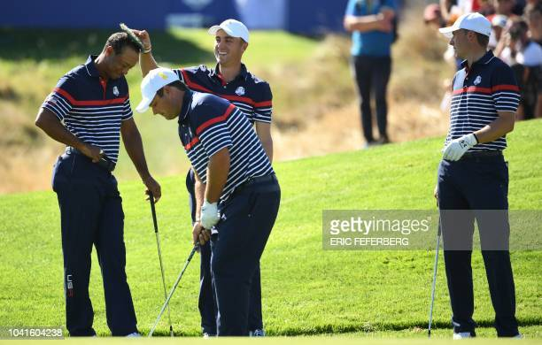 US golfer Tiger Woods smiles with a tuft of grass on his head placed there by US golfer Justin Thomas as US golfer Patrick Reed plays a shot while US...
