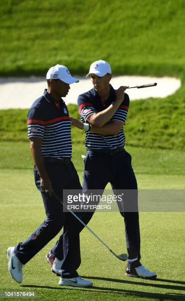 US golfer Tiger Woods speaks with teammate US golfer Jordan Spieth during a practice session ahead of the 42nd Ryder Cup at Le Golf National Course...
