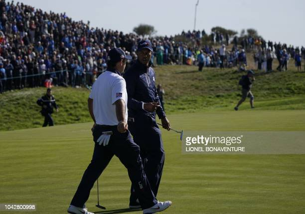US golfer Tiger Woods speaks with US golfer Patrick Reed during their fourball match on the second day of the 42nd Ryder Cup at Le Golf National...