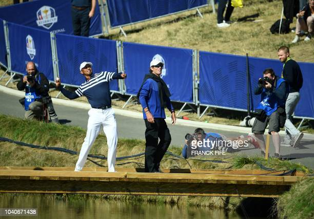 US golfer Tiger Woods throws a ball into the crowd after a practice session ahead of the 42nd Ryder Cup at Le Golf National Course at...