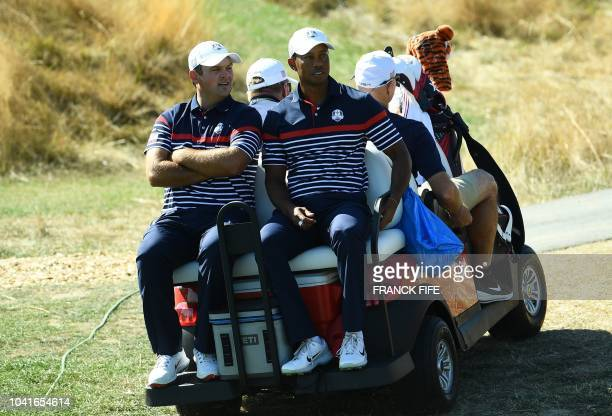 Golfer Tiger Woods travels on a golf buggy with US golfer Patrick Reed during a practice session ahead of the 42nd Ryder Cup at Le Golf National...