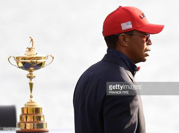 Golfer Tiger Woods walks past the trophy after Europe won the 42nd Ryder Cup at Le Golf National Course at Saint-Quentin-en-Yvelines, south-west of...