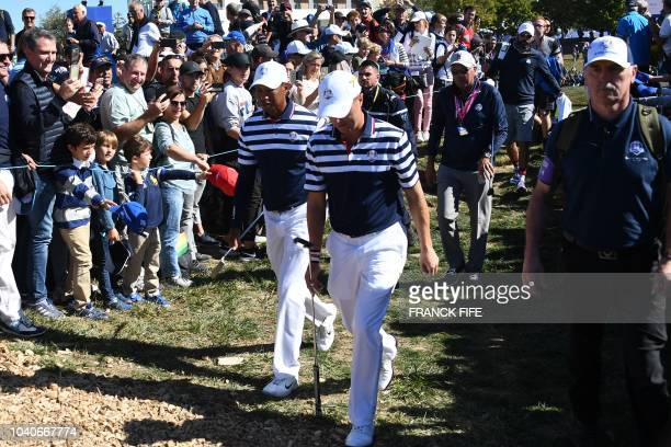 US golfer Tiger Woods walks with US golfer Justin Thomas during a practice session ahead of the 42nd Ryder Cup at Le Golf National Course at...