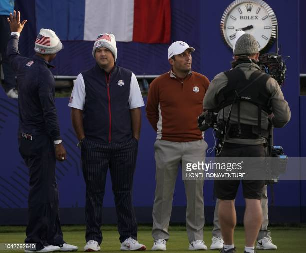 US golfer Tiger Woods waves flanked by US golfer Patrick Reed and Europe's Italian golfer Francesco Molinari during their fourball match on the...