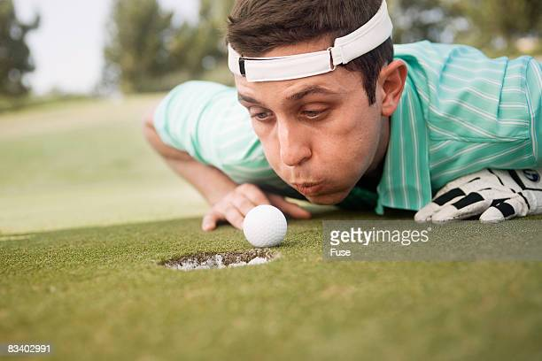 golfer trying to blow ball into cup - golf humour photos et images de collection