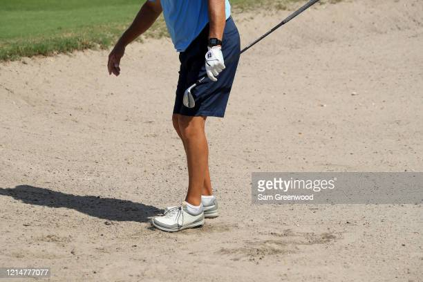Golfer uses his foot to smooth out a bunker at Windsor Parke Golf Club since all rakes have been removed as a part of the 'No Touch' policy amid the...