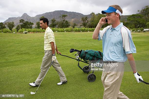 Golfer using mobile phone walking with colleague through golf course, side view