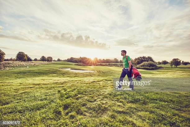 Golfer walking at sunset