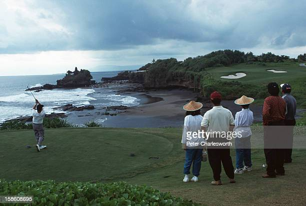 Golfer watched by two caddies drives across the beach towards the green. He is playing the signature hole at the Greg Norman-designed Le Meridien...