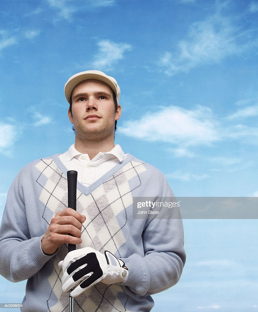 Golfer Wearing a Flat Cap and Holding a Golf Club : Stock Photo