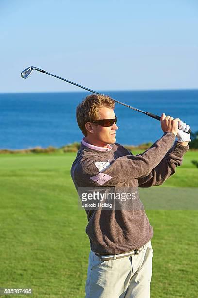 Golfer wearing sunglasses taking golf swing looking away