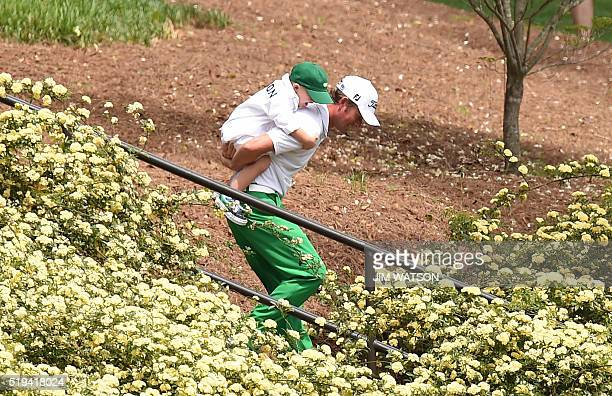 US golfer Webb Simpson carries Bubba Watson's son Caleb on his back as he walks down some staircase during the Par 3 contest prior to the start of...