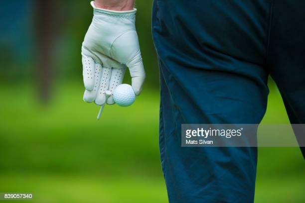 golfer with a golf glove holding a golf ball and a tee. - golf stock-fotos und bilder
