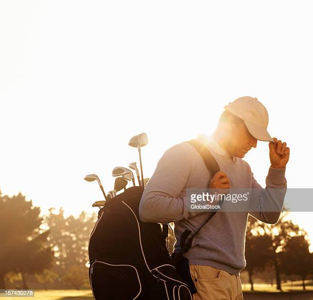 Golfer with his golf kit bag at play