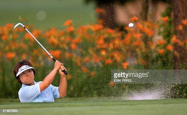 Golfer Yuri Fudoh of Japan blasts out of a sand trap on the eighteenth hole during the third round of the US Women's Open at the Pine Needles Lodge...