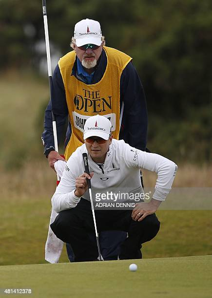 US golfer Zach Johnson and his caddie Damon Green line up a putt on the 12th green during his final round on day five of the 2015 British Open Golf...