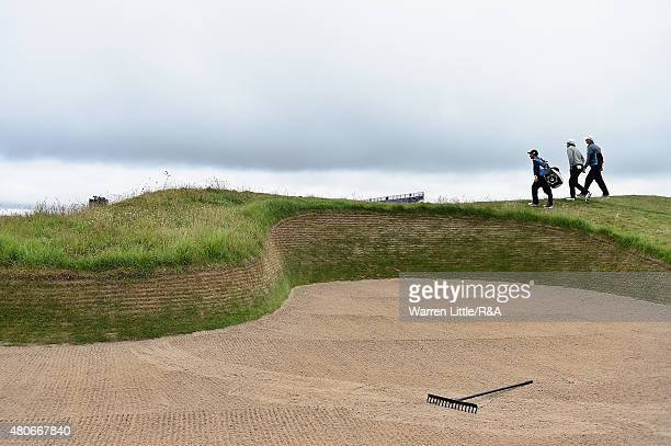 Golfers and a caddie walk to the 14th green past a bunker ahead of the 144th Open Championship at The Old Course on July 14 2015 in St Andrews...